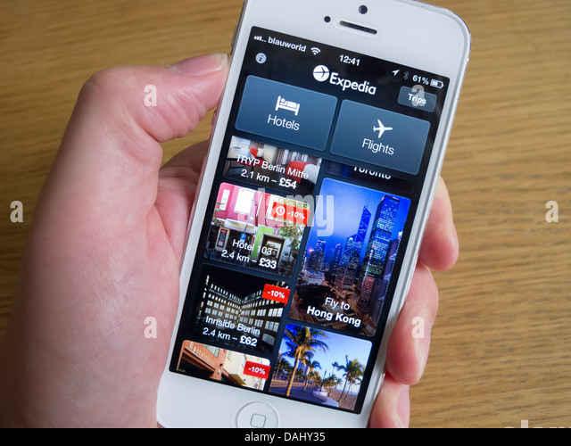 Using Expedia app to book travel on white iPhone 5 smartphone - Stock-Bilder