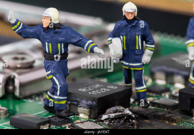 miniature firemen on a computer mainboard - studio shot - Stock Image