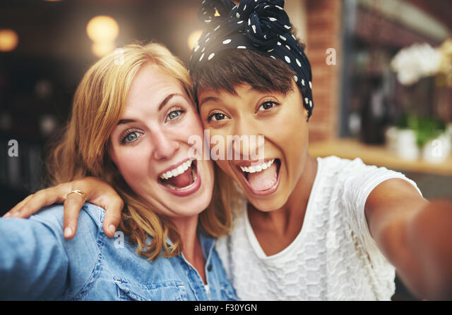 Exuberant happy multi ethnic girl friends enjoying a hearty laugh as they face the camera arm in arm inside a coffee - Stock Image
