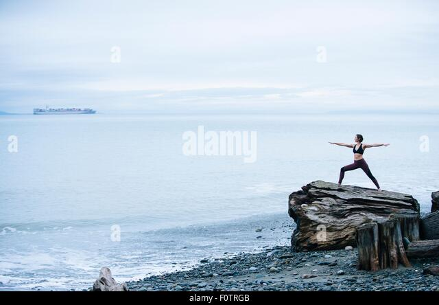 Mature woman practicing yoga pose whilst standing on large driftwood tree stump on beach - Stock Image