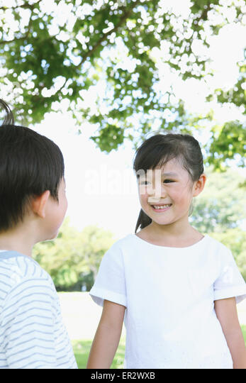 Happy Japanese kids in a city park - Stock Image