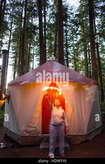Caucasian woman waving sparkler outside yurt - Stock Image