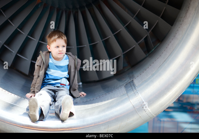 Boy sitting inside aircraft turbine - Stock Image
