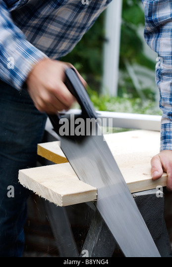 A man using a saw Sweden. - Stock Image