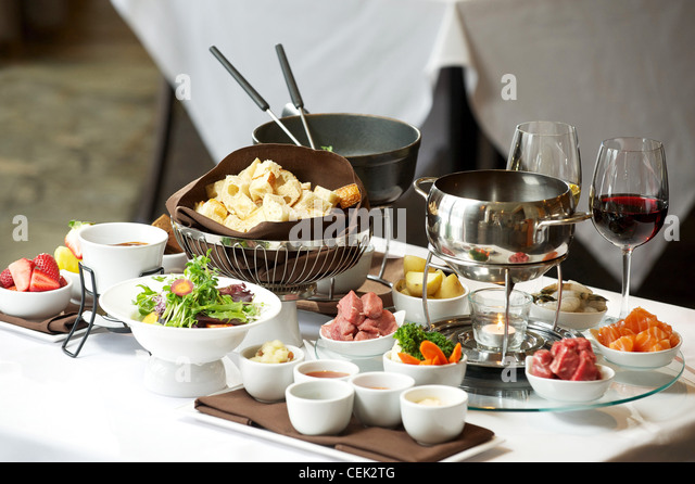 Fondue plate at a restaurant.  Cheese, traditional oil, and chocolate fondue - Stock Image