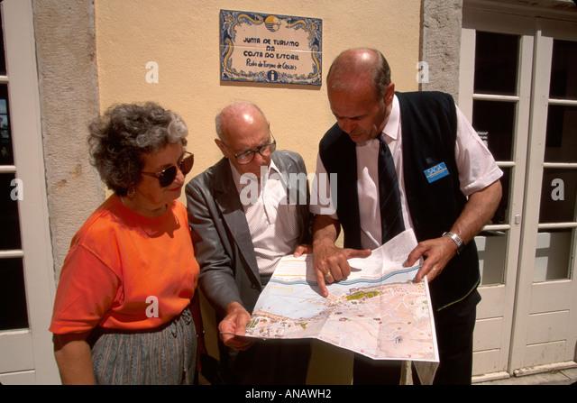 Portugal Cascais Saga Holidays tour guide senior couple map - Stock Image