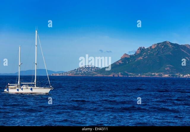 France, Alpes Maritimes, sailboat off the Lerins Islands and the Esterel Mountains in the background - Stock Image