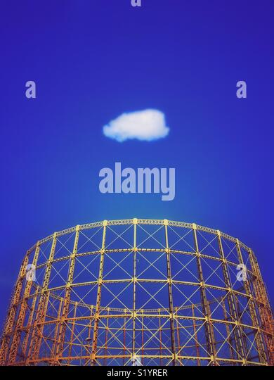 Gasometer structure against a vivid blue sky with solitary white cloud - Stock Image