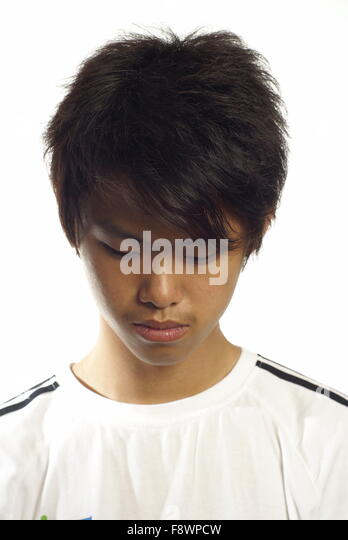 Young asian man looking down with white background - Stock Image