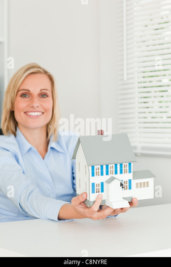 Smiling businesswoman showing model house looks into camera - Stock Image