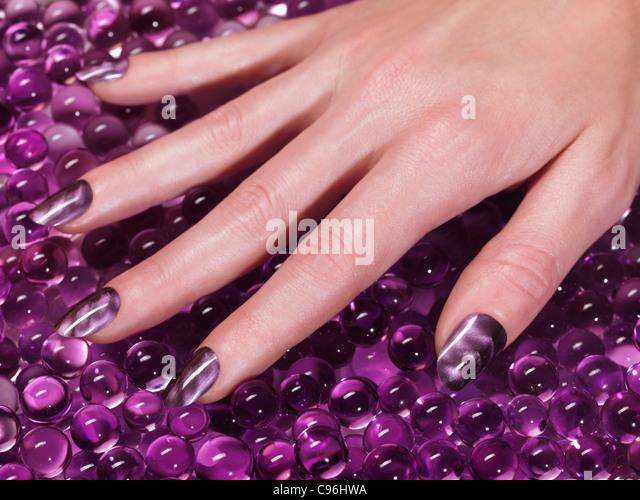 Closeup of woman hand with acrylic nails and purple nail polish - Stock Image