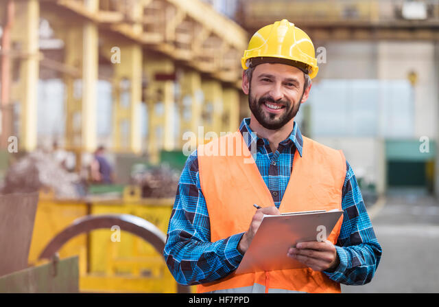 Portrait smiling steel worker with clipboard in factory - Stock Image