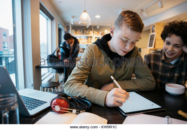 High school boy students studying,using stylus,drawing on digital tablet in cafe - Stock Image