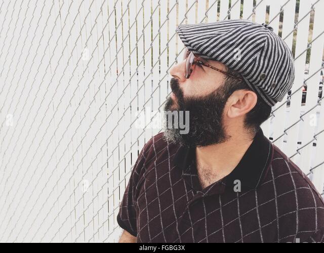 Side View Of Mature Man With Beard Wearing Sunglasses Against Wall - Stock-Bilder