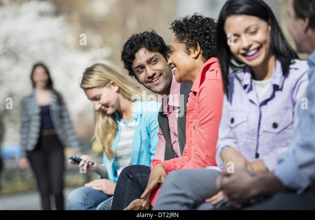 Five people sitting in a row in the park - Stock Image