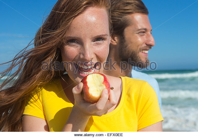 Smiling couple on sunny beach, with woman holding an apple with a bite out of it - Stock Image