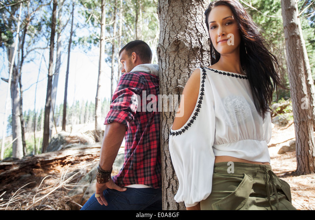 Young couple leaning against tree in forest - Stock-Bilder