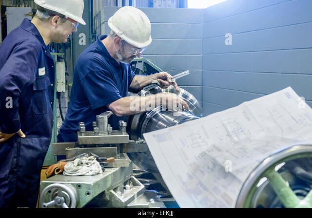 Engineers working on lathe with drawings - Stock-Bilder