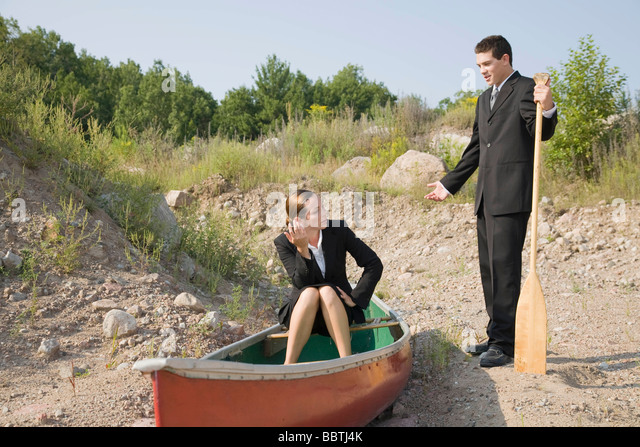 Business people in stranded canoe - Stock Image