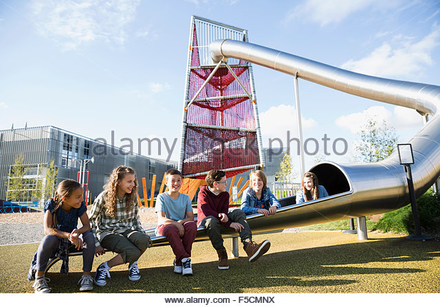 Smiling kids sitting in a row tunnel slide - Stock Image