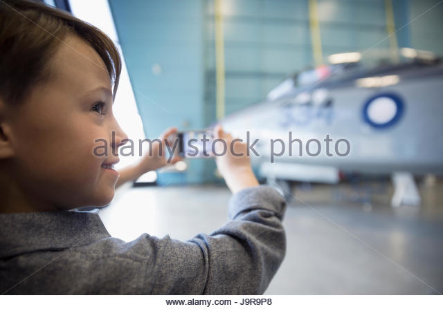 Boy with smart phone photographing Air Force airplane in war museum hangar - Stock-Bilder