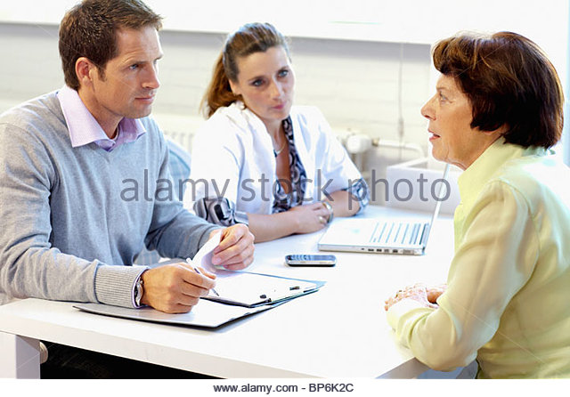 A resident talking to care assistants in a retirement home - Stock Image