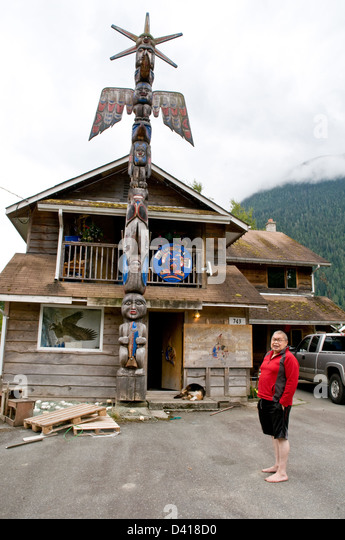 An Nuxalk carver and elder stands beside his totem pole in the native reserve town of Bella Coola, British Columbia, - Stock-Bilder