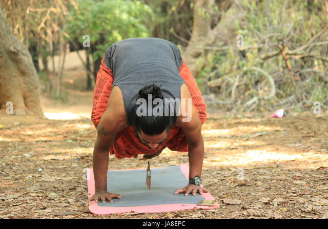Young Indian man performing the crow pose. (Bakasana) Location - Cubbon Park, Bangalore. - Stock Image