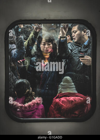 Cramped commuters on the Beijing Metro during rush hour - Stock Image