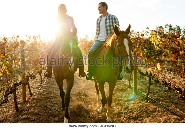 Happy couple talking together while riding chestnut horses through the rows of a colorful autumn vineyard in the - Stock Image