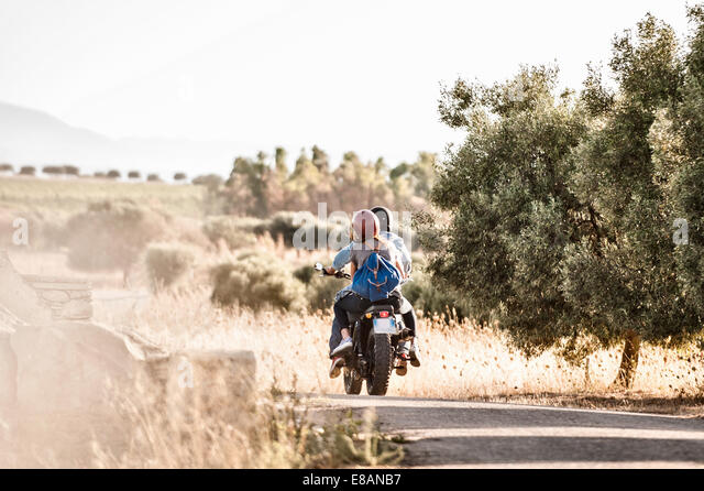 Rear view of mid adult couple riding motorcycle on dusty rural road, Cagliari, Sardinia, Italy - Stock Image