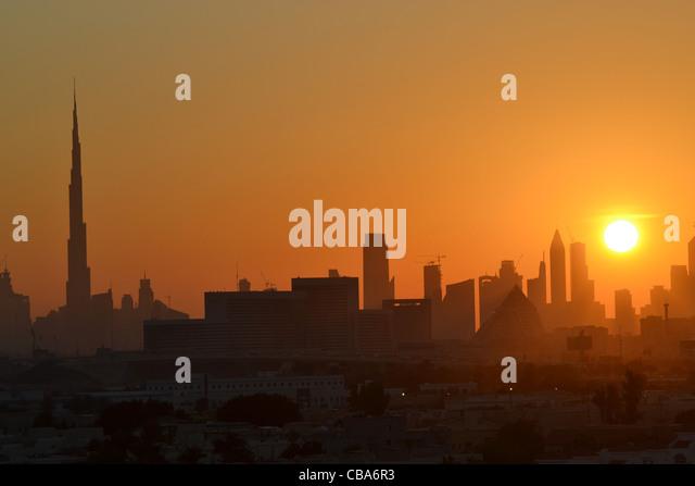 Dubai skyline at sunset with Burj Khalifa on left. - Stock Image