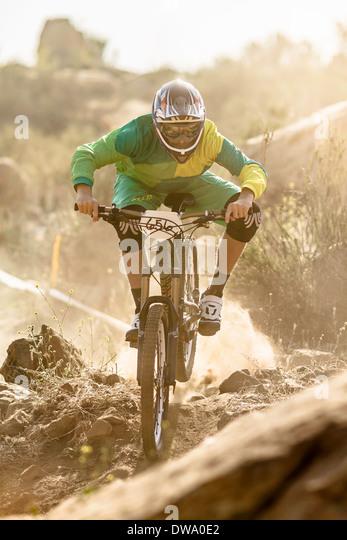 Male mountain biker racing on dusty track, Fontana, California, USA - Stock Image