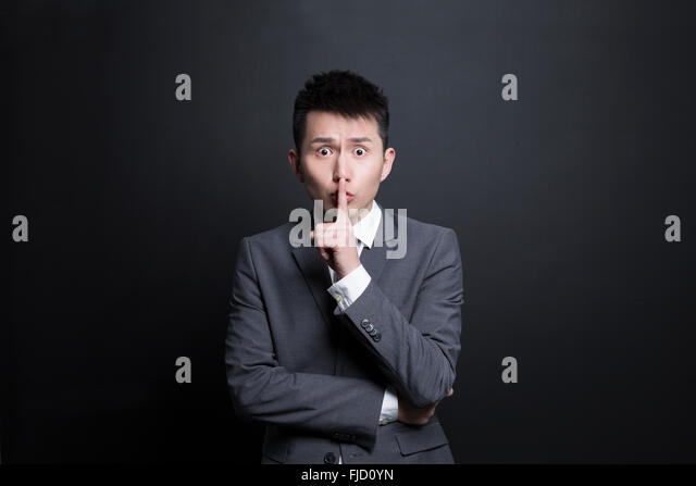 Chinese businessman with finger on lips - Stock Image