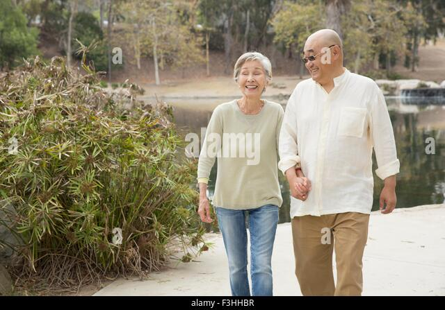 Senior couple walking along pathway, holding hands, laughing - Stock Image