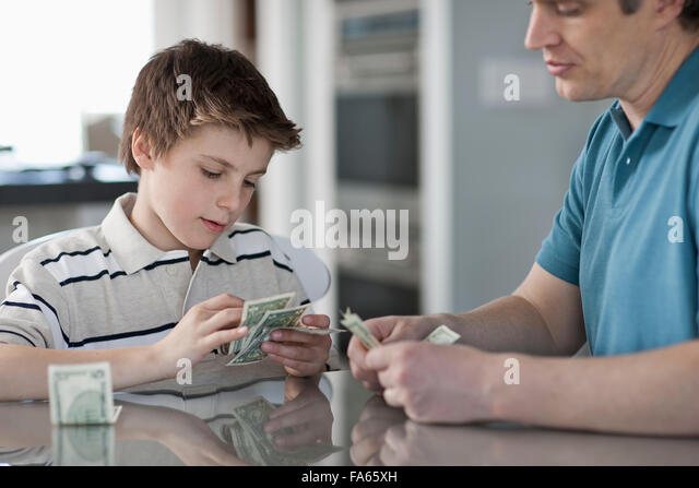 A man and a boy seated at a table, counting and handling cash. - Stock Image