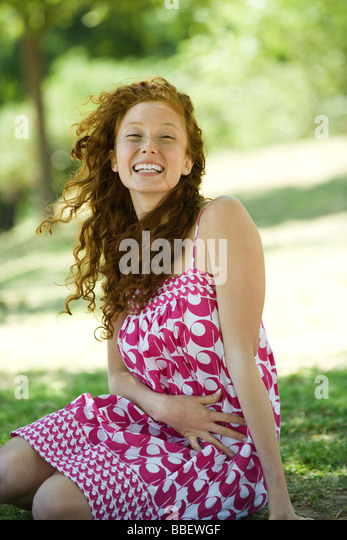 Young red haired woman sitting outdoors, laughing, portrait - Stock Image
