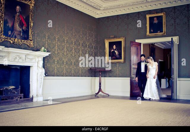 Wedding preparations, Bride and bridegroom walking in mansion, Dorset, England - Stock-Bilder