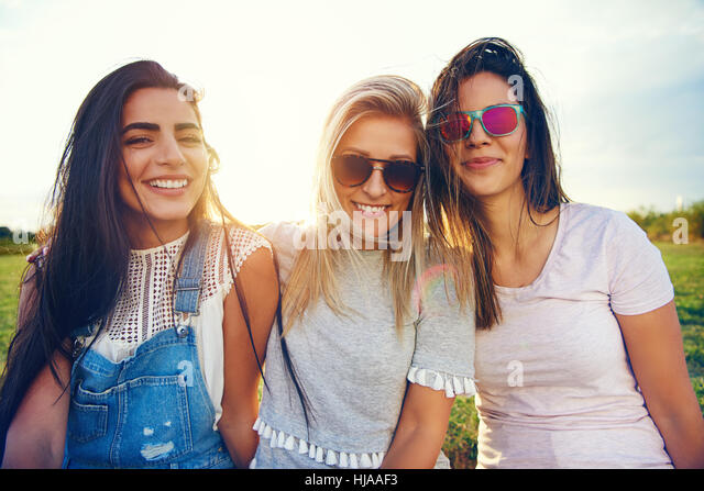 Portrait of three young cheerful girls sitting together and smiling at camera on blurred nature background. - Stock Image