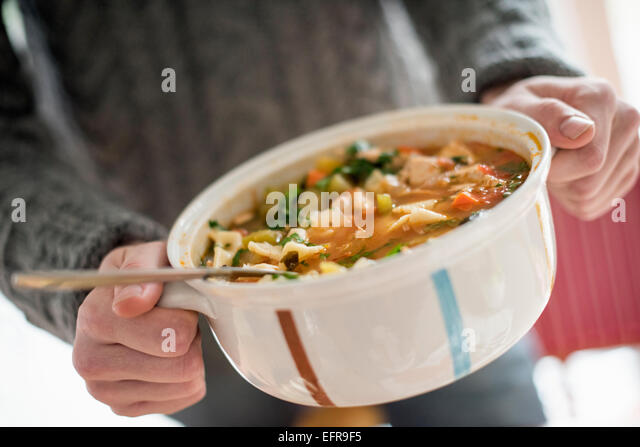 Close up view of a man holding a bowl with a vegetable stew. - Stock Image