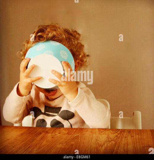 Girl (2-3) holding food bowl to her face - Stock Image