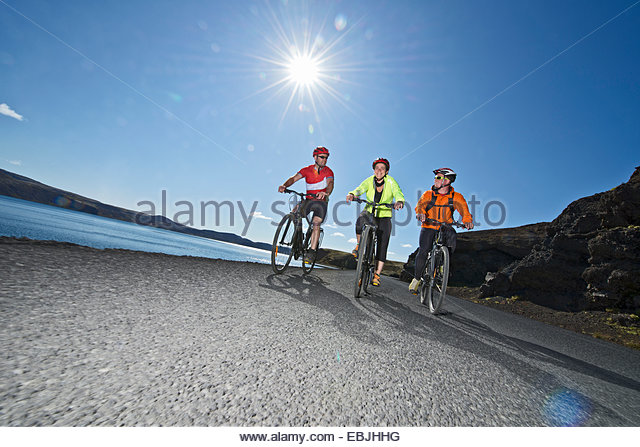 Cyclists cycling on road next to Kleifarvatn, Reykjanes, South West Iceland - Stock Image