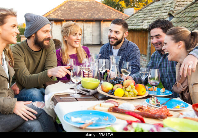 Group of friends drinking wine on garden party - Stock Image