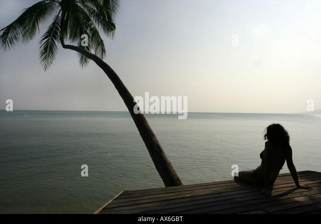 woman with palmtree at the beach - Stock Image