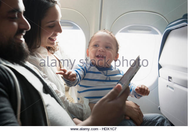Hispanic mother, father and son using digital tablet on airplane - Stock Image