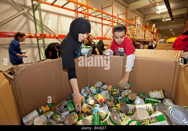 Volunteers Pack Food at Community Food Bank - Stock Image