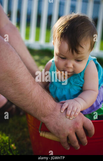 Baby infant standing with the help of her dad and hands on her dad's. - Stock Image