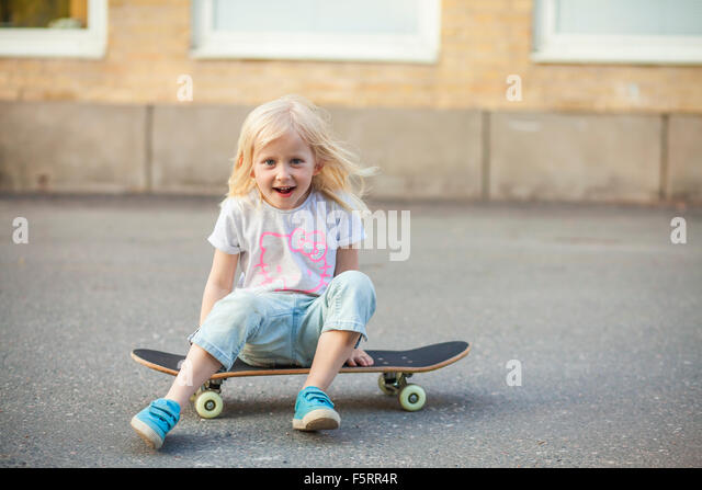 Sweden, Vastergotland, Lerum, Girl (6-7) sitting on skateboard - Stock Image
