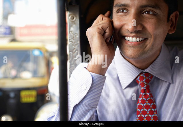 Business man using cell phone, smiling - Stock Image