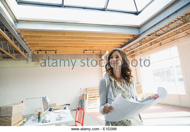 Businesswoman holding blueprints in new office - Stock Image